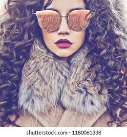 Outdoor fashion photo of young beautiful lady in autumn landscape. Beige coat, fur collar, sunglasses, wine lipstick. Fashion lookbook. Warm Autumn. Warm winter