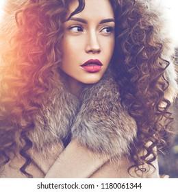 Outdoor fashion photo of young beautiful lady in autumn landscape. Beige coat, fur collar, wine lipstick. Fashion lookbook. Warm Autumn. Warm winter