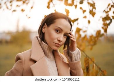 Outdoor-Modefoto von jungen, schönen Dame in beigem Mantel in Herbstlandschaft