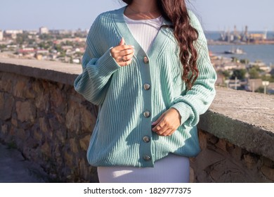 Outdoor fashion photo of young beautiful woman in sea landscape. Lady in warm knitted stylish cardigan