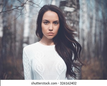 Outdoor fashion photo of young beautiful lady in a birch forest
