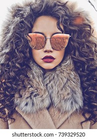 Outdoor fashion photo of young beautiful lady in autumn landscape. Beige coat, fur collar, sunglasses, wine lipstick. Fashion lookbook. Warm Autumn. Warm winter