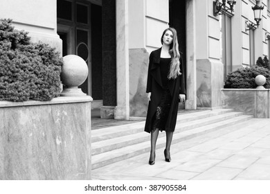 Outdoor fashion photo of young woman in trendy cardigan, black patent leather high heels and bag. Model in nice clothes posing on the city street. Black and white