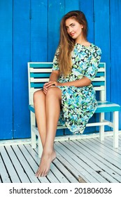 Outdoor fashion portrait of beautiful female model posing outdoor at blue background, wearing stylish midi retro floral dress, have blonde straight hail and perfect tan legs.