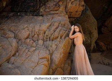 Outdoor fashion portrait of beautiful sensual lady wearing stylish maxi chiffon dress posing at sunset in the beach, have long blonde hairs bright make up and accessorizes
