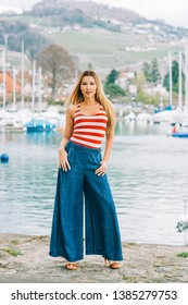 Outdoor fashion portrait of beautiful youn woman posing by the lake, wearing red and white stripe vest and denim wide leg jean