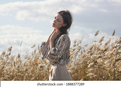 Outdoor fashion portrait of Caucasian woman in wide leg beige pants and patterned blouse.