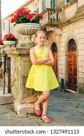 Outdoor fashion portrait of a cute little girl of 8-9 years old on the old street of Tuscany, Italy. Preteen kid wearing green dress and red shoes, vertical image