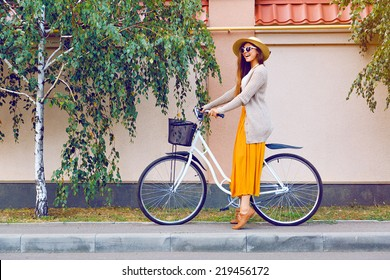 Outdoor fashion portrait of elegant lady riding her hipster retro bike in vintage stylish maxi skirt warm cardigan and straw hat. enjoy mica fall autumn day, posing at the street with birch trees.