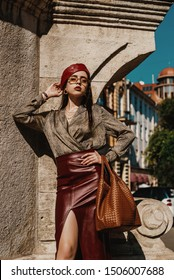 Outdoor fashion portrait of elegant, luxury woman wearing trendy leather  dark red midi skirt, beret, snakeskin print satin blouse, sunglasses, holding brown handbag, posing in street of European city