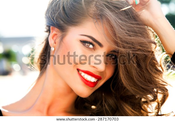 Outdoor fashion portrait of glamour lady with perfect make-up and glowing skin,full red lips,and big eyes posing at sunset,tan model face.Sexy perfect fit body woman.Attractive sexy and young girl