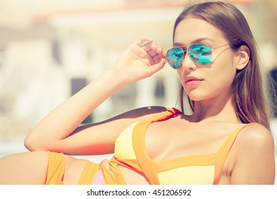 Outdoor fashion portrait of glamour tan woman in sunglasses have sunbath and relaxing near pool.Wearing stylish swimwear and laying on deck chair.