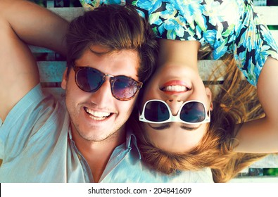 Outdoor fashion portrait of happy smiling couple in love having fun together end enjoy their love and romantic date.