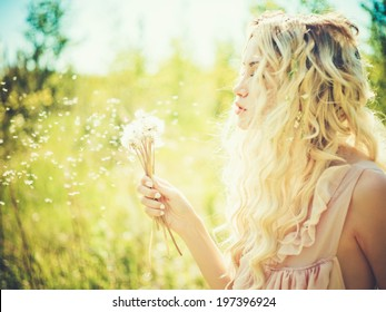 Outdoor fashion portrait of romantic blonde with dandelions