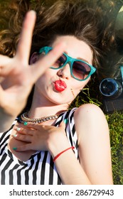 Outdoor fashion portrait of stylish girl showing peace sign to camera,wearing bright summer colored sunglasses.perfect skin and full red lips,nice smile,curly hair,with sequins with hand watch,fall