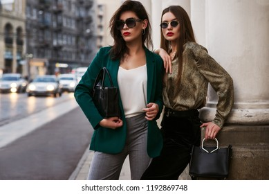 Outdoor fashion portrait of two young beautiful women wearing trendy sunglasses, stylish clothes, holding black leather bags, posing in street of european city. Copy, empty space for text