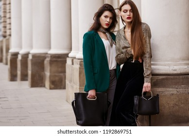 Outdoor fashion portrait of two young beautiful women wearing trendy clothes, accessories with animal print, holding black leather bags, posing in street of european city. Copy, empty space for text