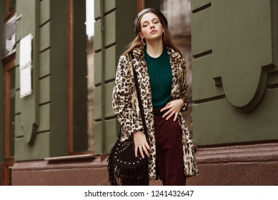 Outdoor fashion portrait of woman wearing trendy animal, leopard print faux fur coat, beret, sweater, corduroy trousers, carrying suede bag with fringe, posing in street of city. Copy, empty space
