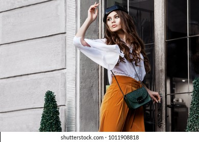Outdoor fashion portrait of young beautiful woman wearing stylish clothes, with small leather bag, posing near the door. Model looking aside. Copy, empty space for text