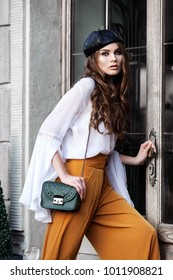 Outdoor fashion portrait of young beautiful woman wearing stylish clothes, beret, holding small green leather bag, posing near the door. Model looking at camera.