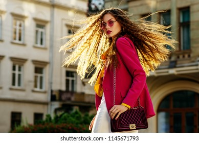 Outdoor fashion portrait of young beautiful woman with very long hair wearing stylish round pink sunglasses, fuchsia color blazer,  holding violet bag, walking in street of european city. Copy space