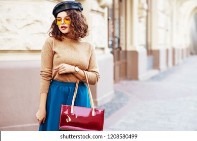 Outdoor fashion portrait of young beautiful  woman wearing stylish leather beret, orange sunglasses, wrist watch, cashmere turtleneck, midi blue skirt, holding red bag, posing in street. Copy space