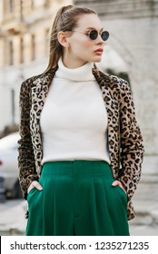 Outdoor fashion portrait of young beautiful confident woman wearing trendy leopard print blazer, white turtleneck, green high-waisted trousers, stylish sunglasses, posing in street of european city