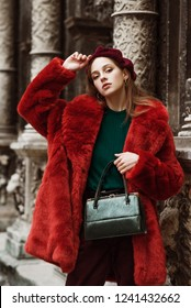Outdoor fashion portrait of young beautiful confident woman wearing trendy orange faux fur coat, beret, green sweater, corduroy trousers, holding stylish snakeskin handbag, posing in street of city