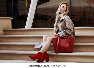 Outdoor fashion portrait of young beautiful fashionable woman wearing trendy beige long trench coat, red suede ankle boots, heels, holding big tote bag, sitting on stairs. Copy, empty space for text