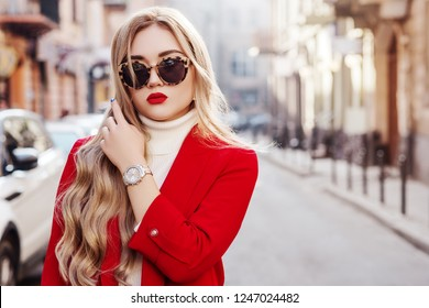 Outdoor fashion portrait of young beautiful fashionable lady wearing stylish turtle frame sunglasses, luxury wrist watch, white turtleneck, red blazer, posing in street of european city. Copy space