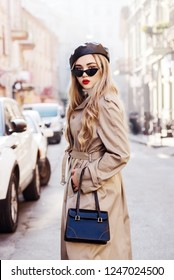 Outdoor fashion portrait of young beautiful fashionable girl wearing trendy beige long trench coat, stylish cat eye sunglasses, leather beret, holding handbag, model posing in street of european city