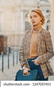 Outdoor fashion portrait of young beautiful fashionable girl wearing trendy checkered blazer, beige turtleneck, high-waisted jeans, wrist watch, carrying green blue handbag, posing in street
