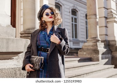 Outdoor fashion portrait of young beautiful fashionable girl wearing blue checkered dress, grey coat, leather beret, sunglasses, holding small bag, posing in european city. Copy, empty space
