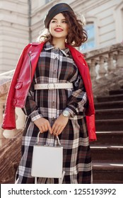 Outdoor fashion portrait of young beautiful fashionable girl wearing autumn long checkered dress, red leather biker jacket, beret, belt, wrist watch, holding white bag, posing in european city