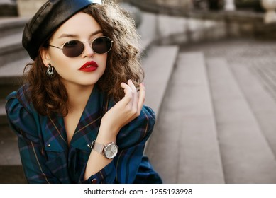 Outdoor fashion portrait of young beautiful fashionable girl wearing trendy sunglasses, wrist watch, earrings, leather beret, blue checkered dress, posing in street, on stairs. Copy, empty space