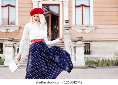 Outdoor fashion portrait of young beautiful woman wearing red beret, belt, turtleneck, polka dot blue midi skirt, holding small white leather bag, posing in old european street. Copy, empty space