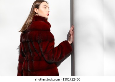 Outdoor  fashion portrait of young beautiful confident woman wearing trendy red faux fur coat, hat, posing in street of european city. Horizontal shot