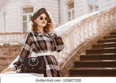 Outdoor fashion portrait of young beautiful fashionable lady wearing trendy  long checkered dress, leather beret, sunglasses, holding stylish bag, posing in european city. Copy, empty space for text