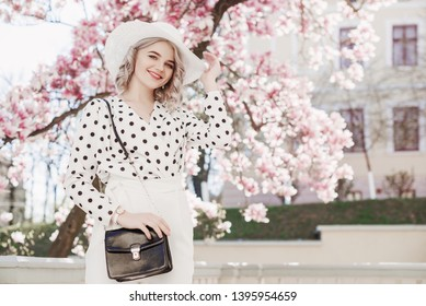 Outdoor fashion portrait of young beautiful happy smiling lady wearing  stylish white hat, wrist watch, polka dot blouse, holding small bag, posing in street with blooming magnolia tree. Copy space