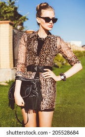 Outdoor fashion portrait of young beautiful stylish woman wearing mini printed dress casual black leather bag with spikes, and retro cat eye sunglasses.