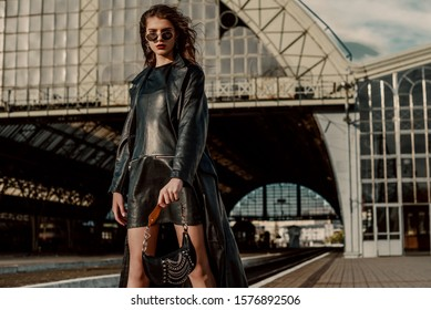 Outdoor fashion portrait of young confident model, woman wearing trendy sunglasses, black leather trench coat, dress, with small hobo handbag, posing in street of city. Copy, empty space for text