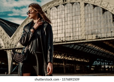 Outdoor fashion portrait of young confident model, woman wearing trendy black leather trench coat, dress, wrist watch, with small hobo bag, posing in street of city. Copy, empty space for text
