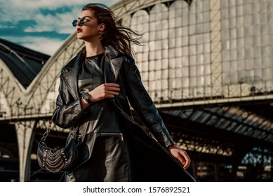 Outdoor fashion portrait of young confident model, woman wearing trendy black leather trench coat, dress, glasses, wrist watch, with small hobo bag, walking in street of city. Copy, empty space