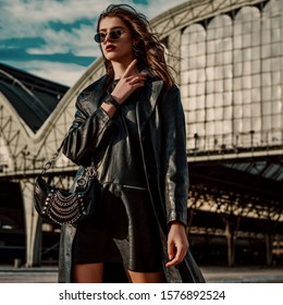 Outdoor fashion portrait of young confident model, woman wearing trendy black leather trench coat, dress, sunglasses, wrist watch, with small hobo bag, posing in street of city. Copy, empty space