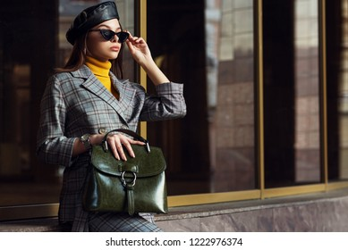 Outdoor fashion portrait of young elegant businesswoman, woman wearing sunglasses, beret, checked suite, blazer, turtleneck, holding green leather bag, posing in street of european city. Copy space