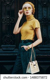 Outdoor fashion portrait of young elegant lady wearing colorful outfit: yellow beret, glasses, turtleneck, green trousers, wrist watch, holding stylish white bag, posing in street