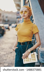 Outdoor fashion portrait of young elegant lady wearing colorful outfit: yellow beret, glasses, turtleneck, green trousers, golden wrist watch, holding stylish white bag, posing in street