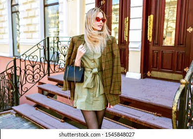 Outdoor fashion portrait of young elegant woman wearing trendy oversized jacket, mini dress and small leather black bag, posing on Paris street , toned warm colors.