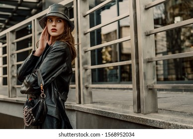 Outdoor fashion portrait of young elegant model, woman wearing trendy bucket hat, black leather trench coat, holding small hobo bag, handbag, posing in street of European city. Copy space for text