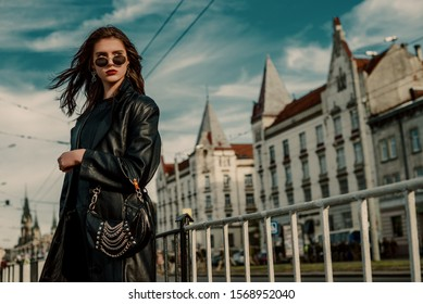 Outdoor fashion portrait of young elegant model, woman wearing trendy sunglasses, black leather trench coat, with small hobo handbag,  posing in street of European city. Copy, empty space for text